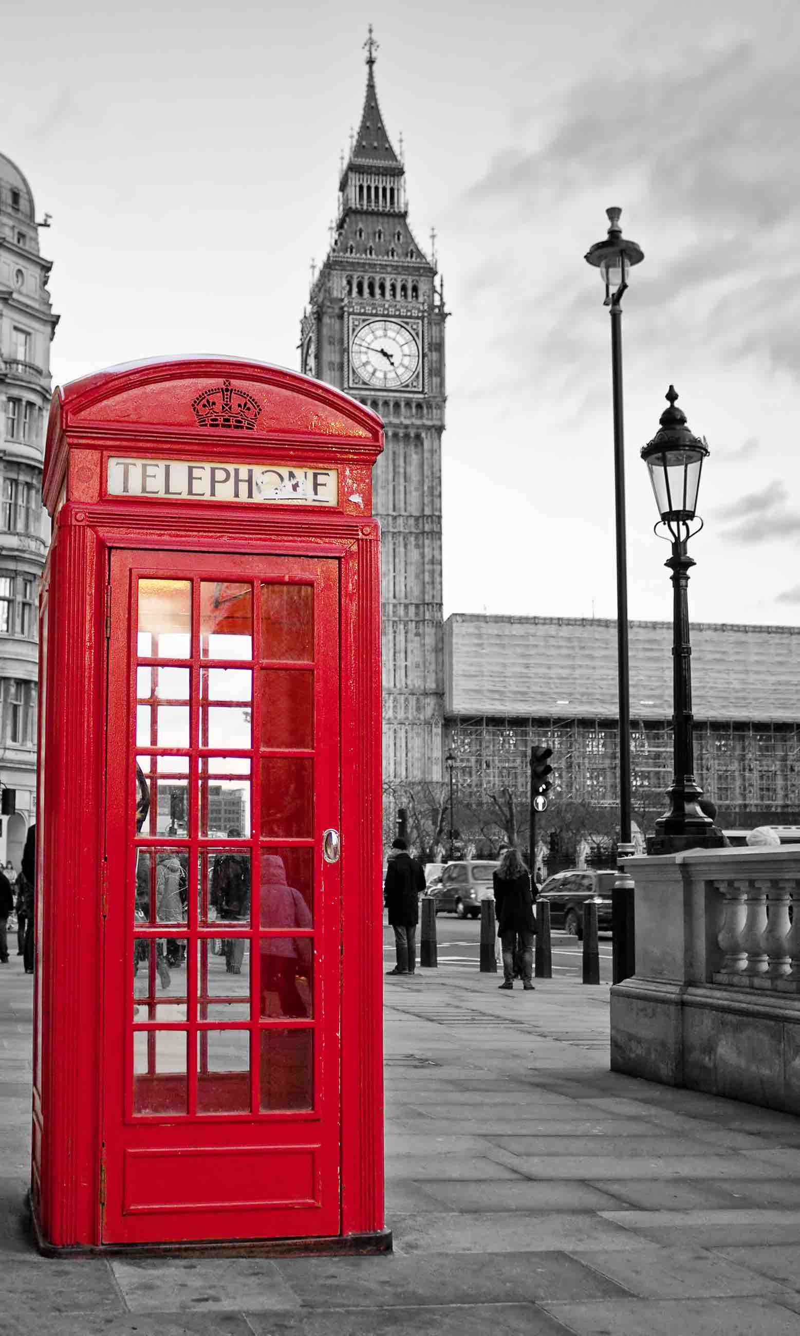 A  traditional red phone booth in London with the Big Ben in a black and white background